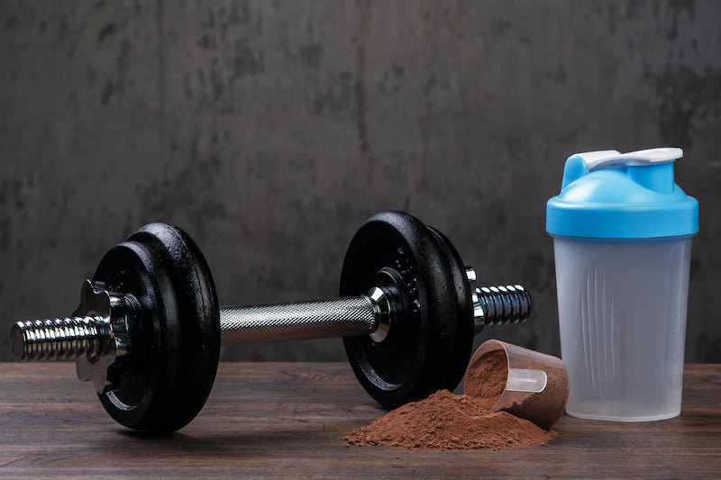 Mass gainer protein powder next to an empty shaker bottle and a dumbbell