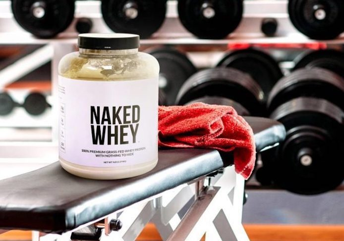 Tub of Naked Whey placed on a workout bench in a gym