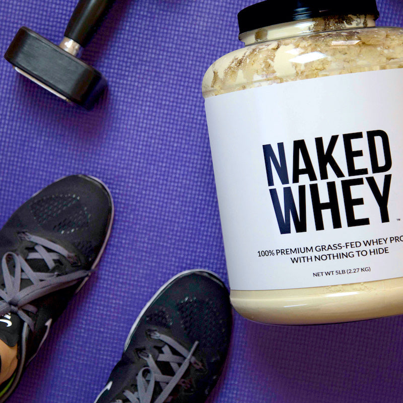 Tub of Unflavored Naked Whey on a gym mat next to a pair of gym shoes and a weight