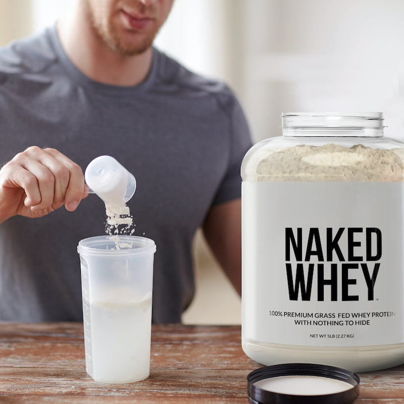Man making a protein shake with Naked Whey, putting a scoop of the protein powder into a blender bottle on a counter