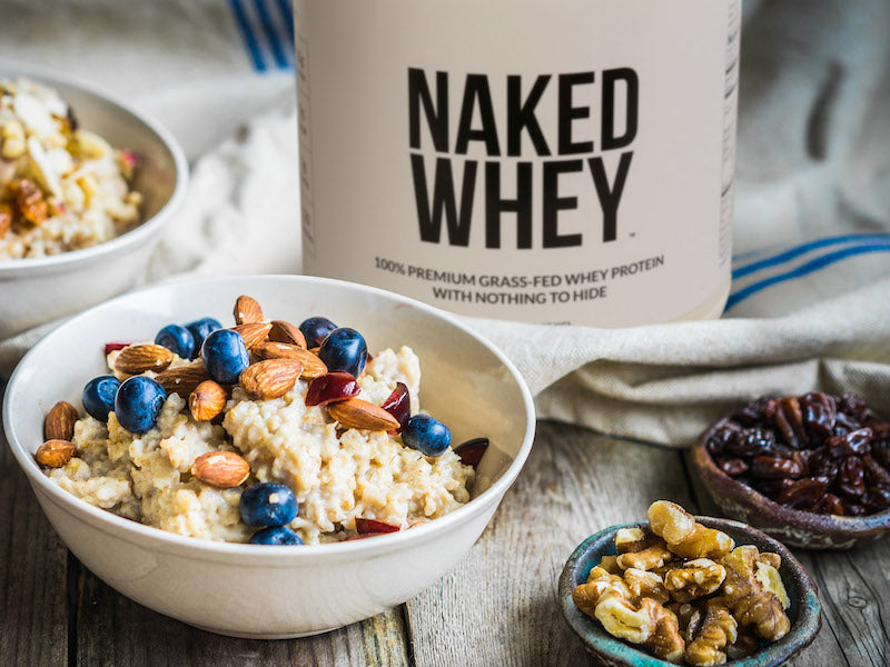 Tub of Naked Whey behind a bowl of cooked oatmeal topped with blueberries and nuts