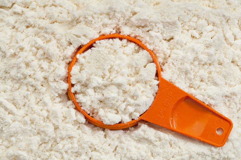 Orange plastic scoop on top of a heap of whey protein powder