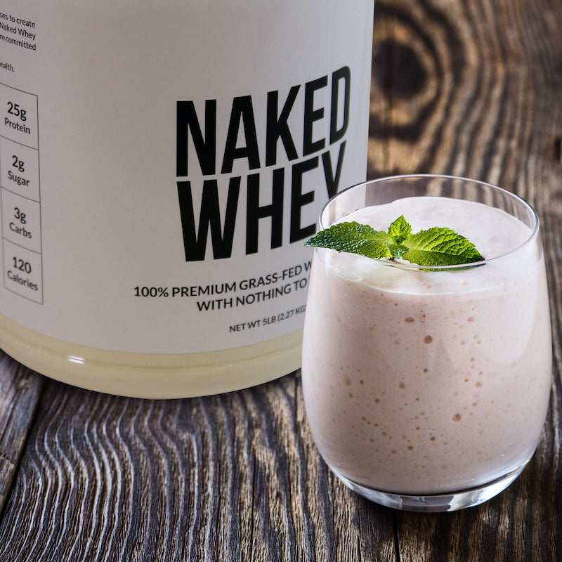 Tub of Naked Whey next to a protein shake in a small glass
