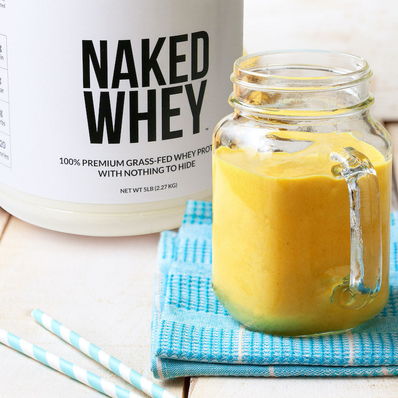 Tub of Unflavored Naked Whey next to a fruit protein shake in a clear glass