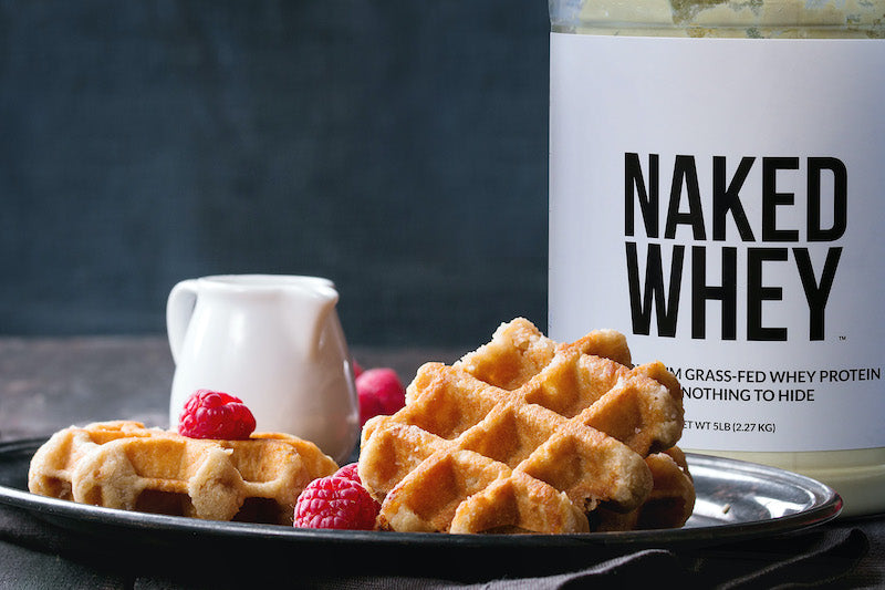 A tub of Naked Whey behind a plate of waffles and berries