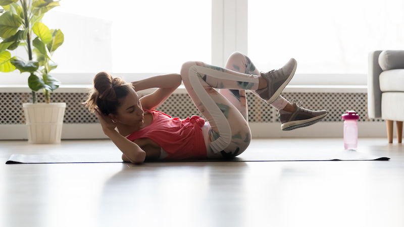 Woman in gym clothes gear doing crunches at home