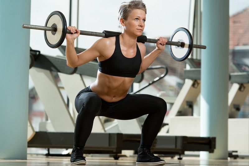 Woman lifting a barbell weight in a gym setting