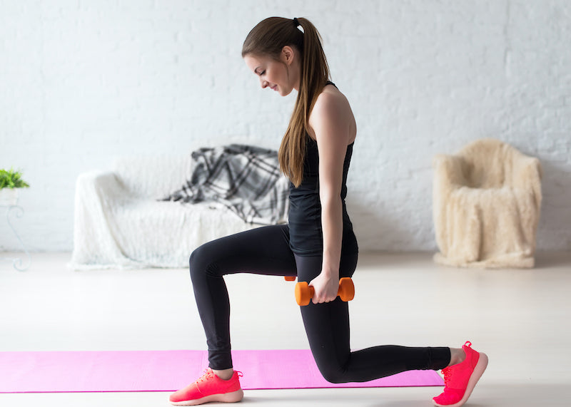 Woman in an empty room doing lunges while holding dumbbells