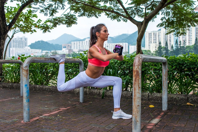 Athletic woman doing single leg split squat exercise with park equipment outdoors with high buildings in background.