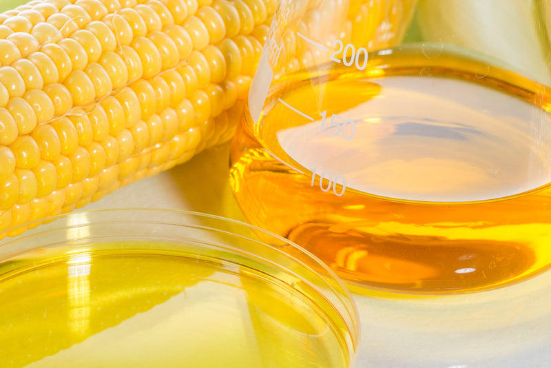 Glass container of corn syrup next to a cob of corn