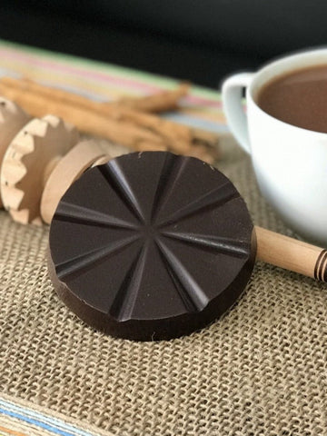 chocolate disk on burlap napkin with cup in background