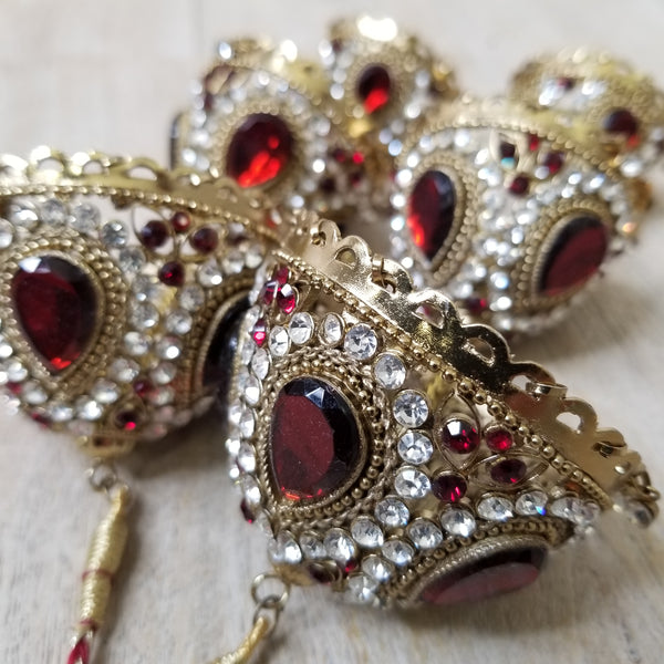 Kaleeray in gold metal, covered in clear and red rhinestones usually attached to indian bangles