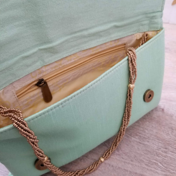 open purse in mint green with zipper pocket and gold bead chain, inspired by south asian designs