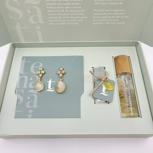 Full boxed view of gift set containing oval shaped citrine earrings dangling from gold plated mini zirconia white semi-precious stones paired with essential oils and selenite crystal carrier.
