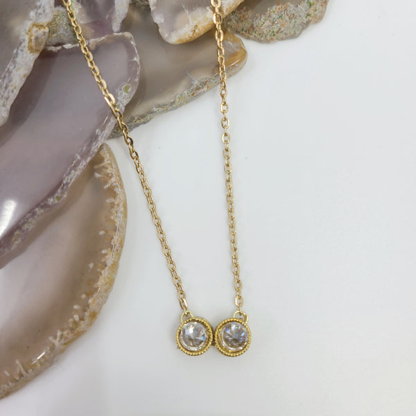 Attractive necklace which the pendant looks like tiny opera glasses, these stylish white zircon stones are elegantly fashioned inside 14K gold plated frames.