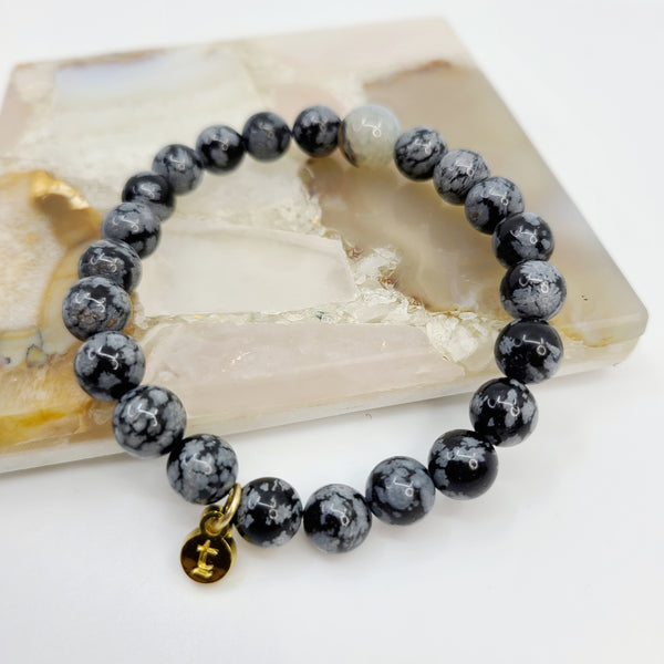 Jasper colored black and blue-grey beaded bracelet laying over a marble slab to highlight contrast of markings on each bead.