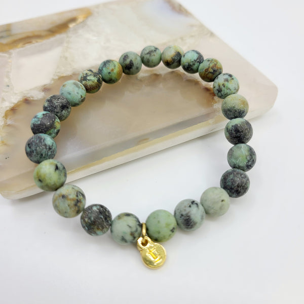 Contrast view of beaded bracelet showcasing the range of earth tones in this emerald gemstone bracelet.