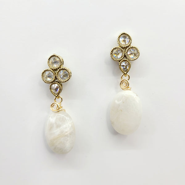 Stunning shine and reflection bounce off of this up close view of pearly white moonstone earrings fastened by hand wrapped 14K gold plated cubic zirconia diamond studs.
