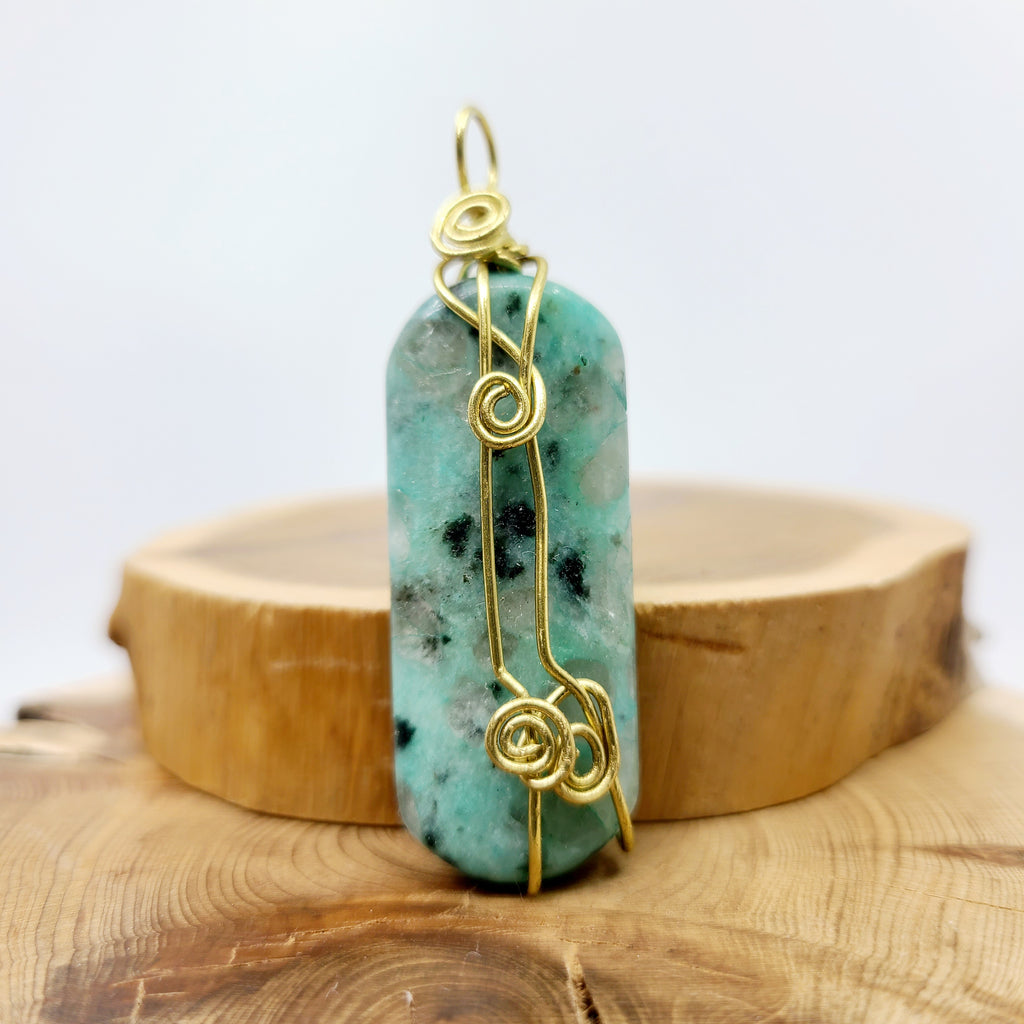 Turquoise opaque pendant decorated by nature with flecks of black and grey stone colours and is hand wrapped with precision witnessed by the delicate spiral design.