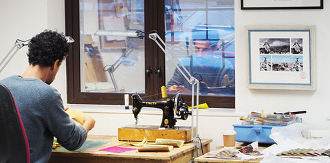 Tovi Sorga handcrafting fashion accessories at his sewing machine in the Bristol studio