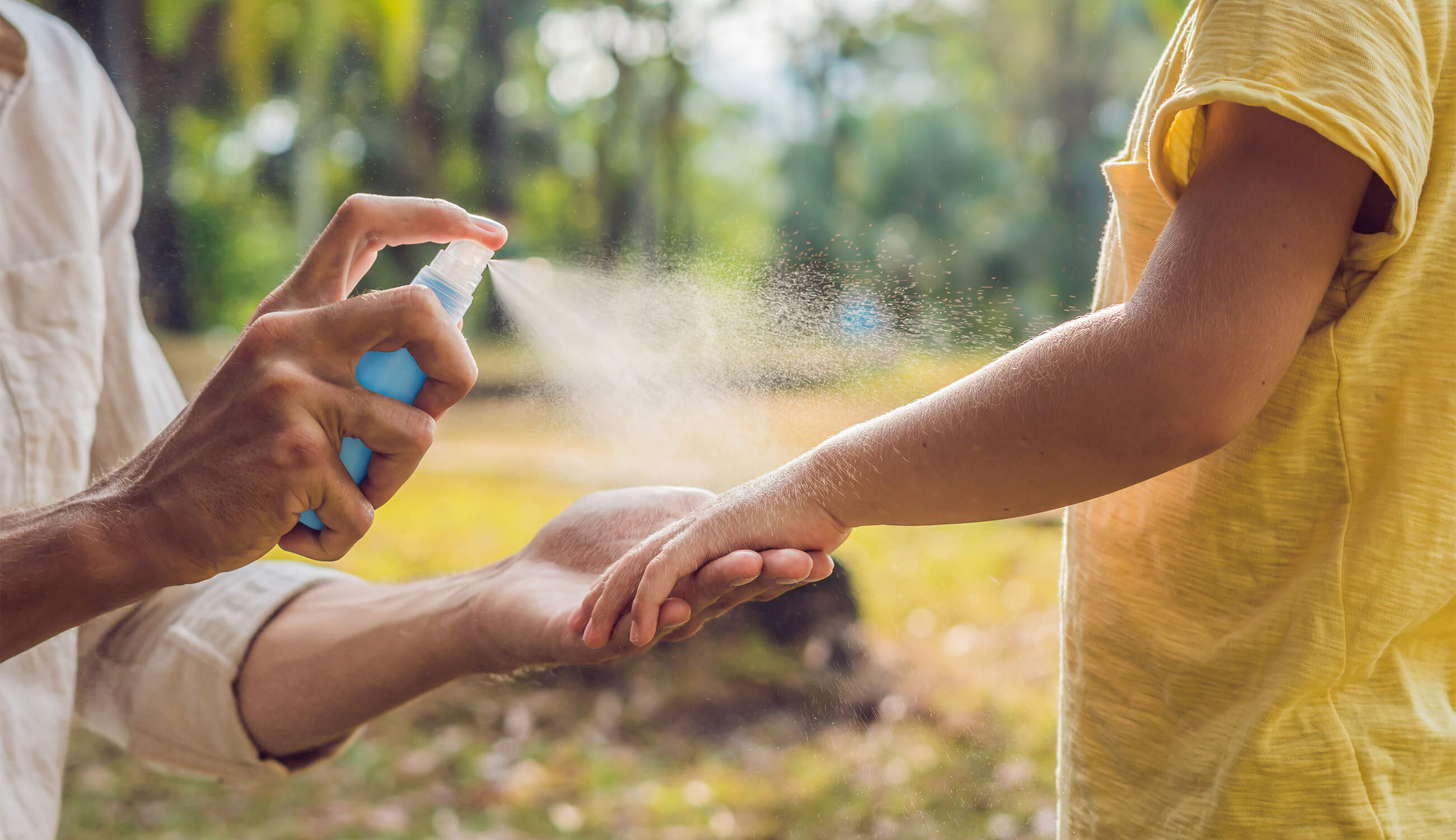 Main_spraying insect repellent on skin outdoor