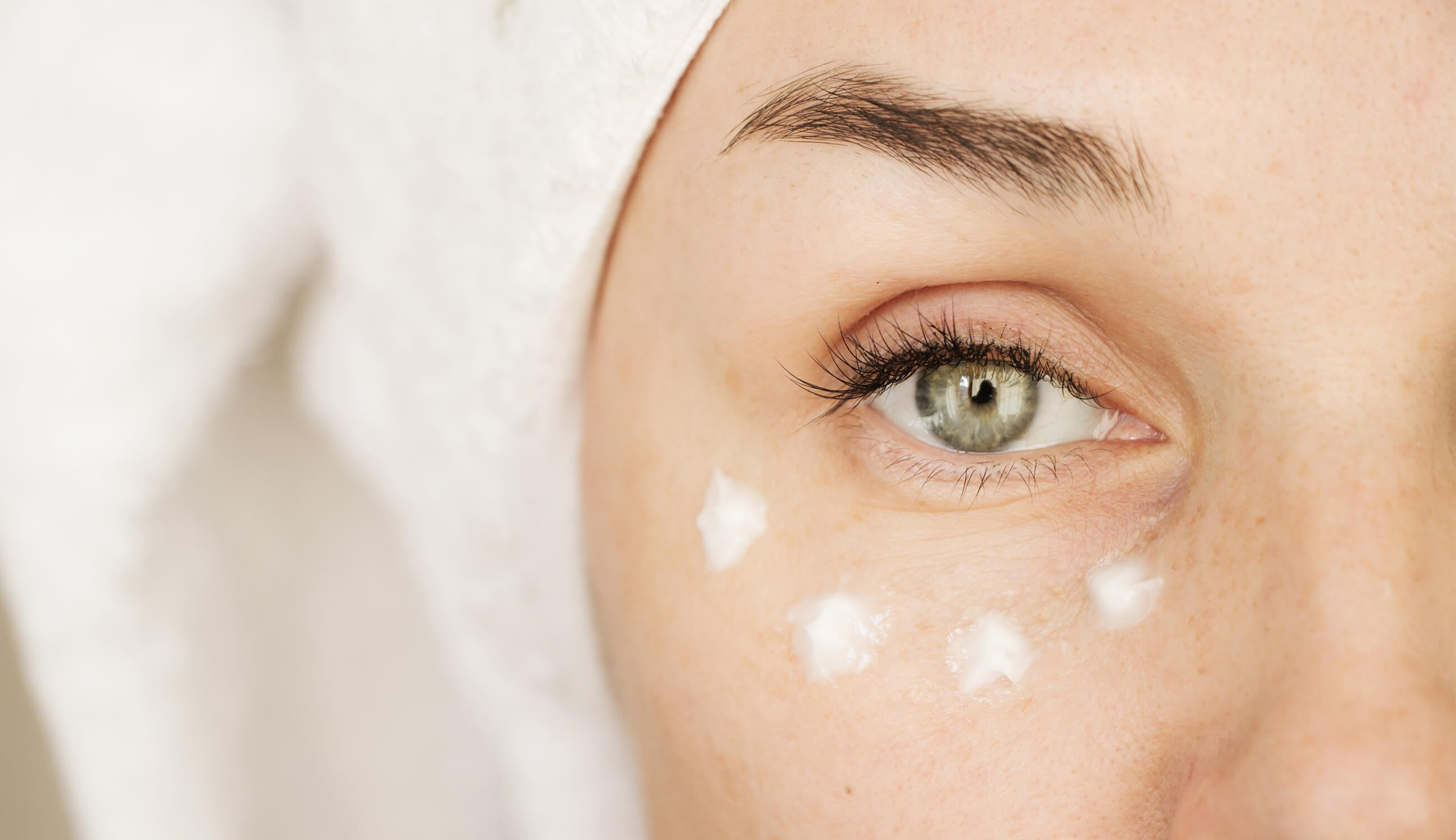 woman puts cream on her face.jpg