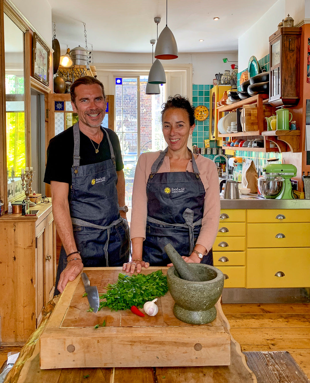 Founders John and Emily in their Food at 52 signature denim aprons teaching the first online cooking class.