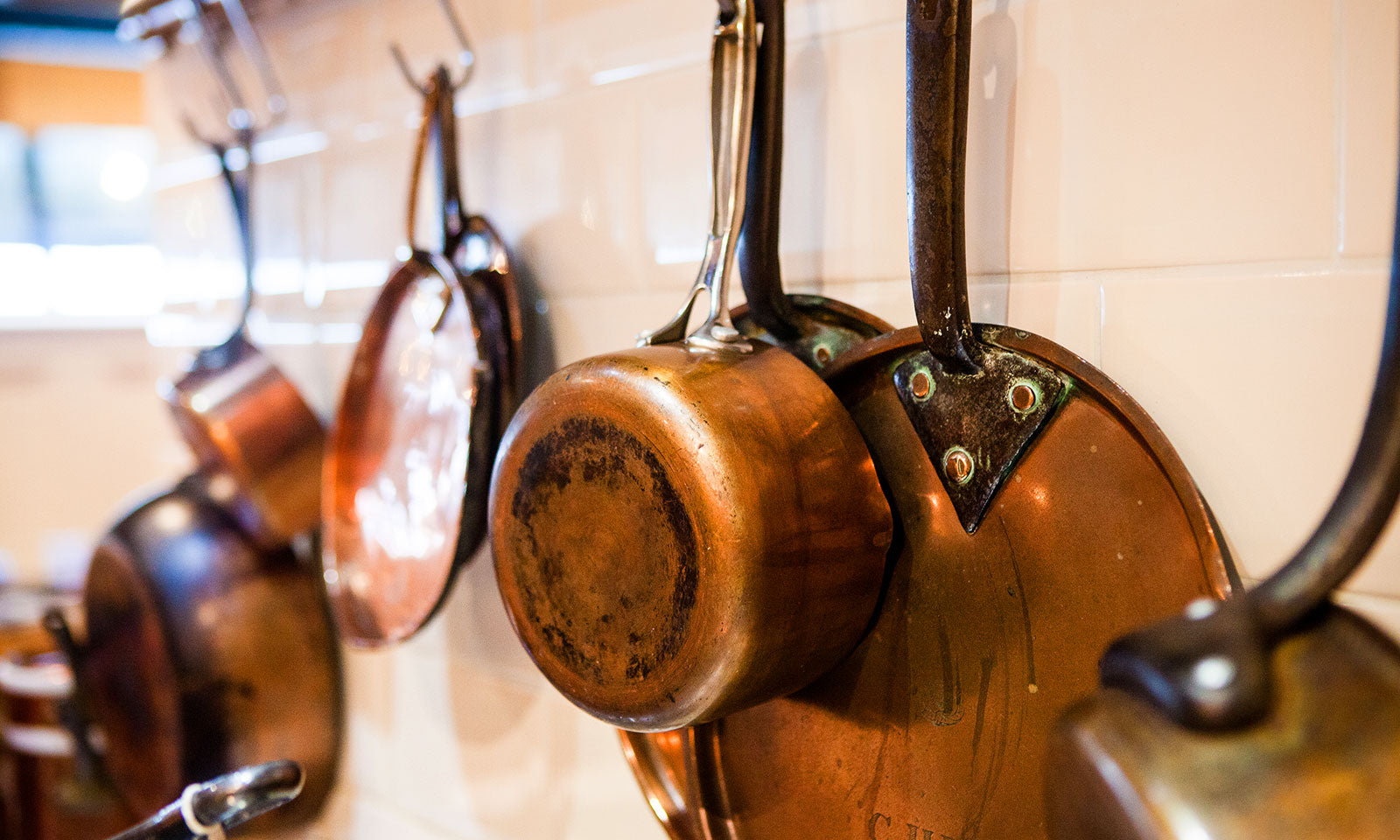 Copper cookware completes the cottage kitchen effect.