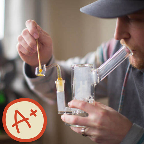man hitting a clean dab rig with a A+ sticker lower left