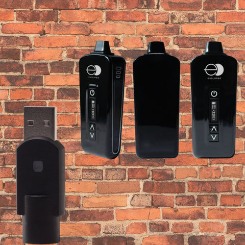eclipse black vaporizer with black usb charger. Brick wall