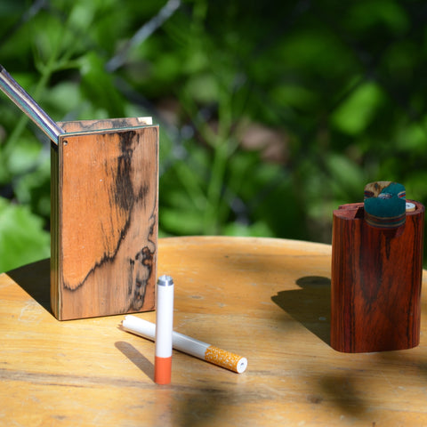 Two - One hitter wooden dugouts on a wooden stool outside