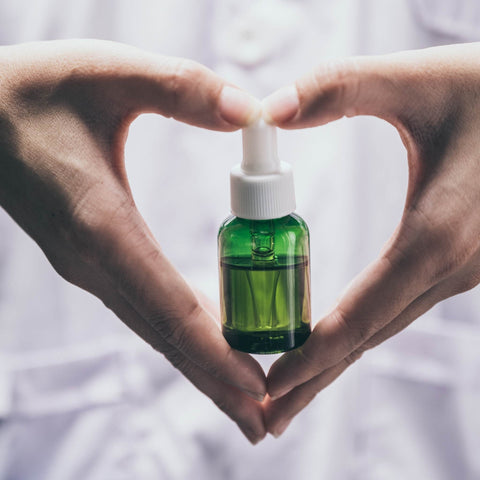 cbd green tincture held in the hands of someone