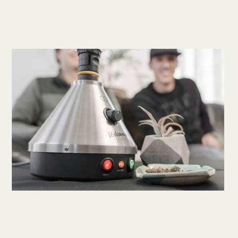 Desktop Vaporizer on a table with two friends sitting on a couch