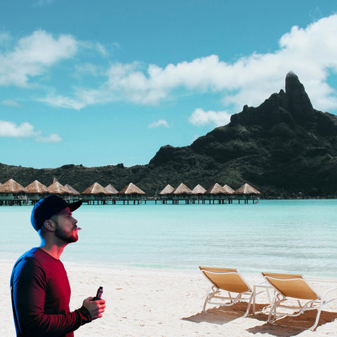 man sitting on a beach with a vape on vacation