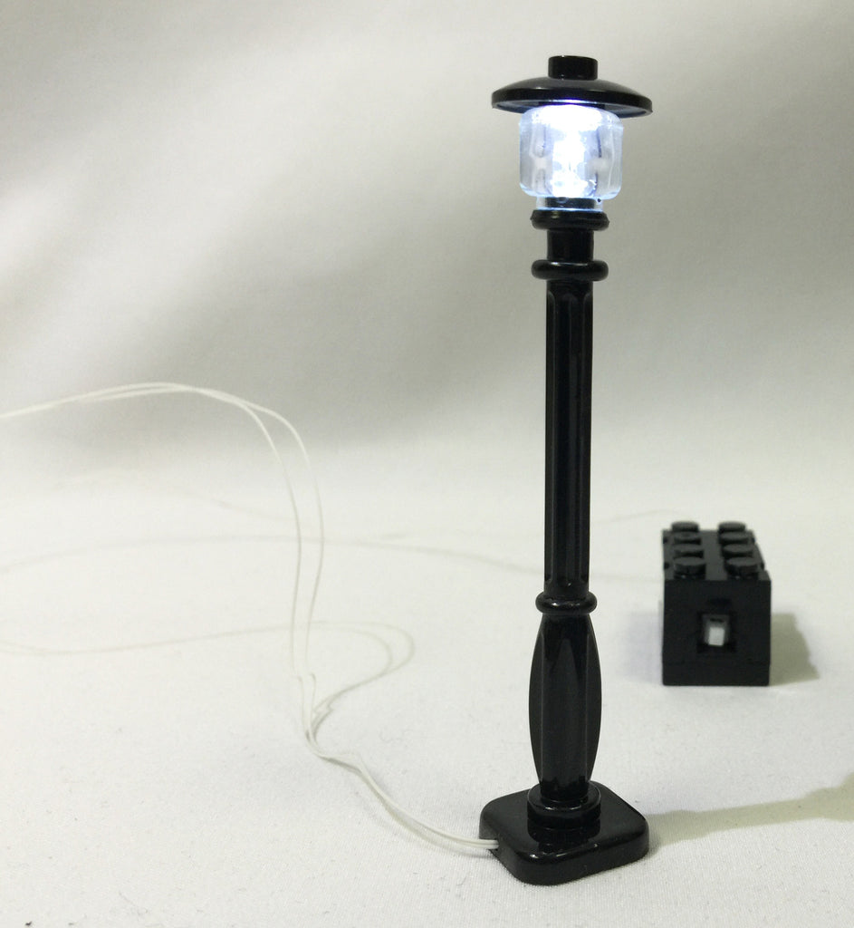 Brick Loot LED Lighting for LEGO Cities - Black Street Lamp / Lamp Post Light with black 2x4 battery brick (2 AG3 batteries, included). The street lamp in this photo is on.