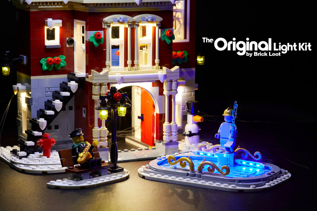Close up of the  LEGO Winter Village Fire Station set , fully illuminated with the Brick Loot Custom LED Light kit! Beautiful LED lights light up the inside and outside of the Fire Station, black lamp post, and ice skating rink!