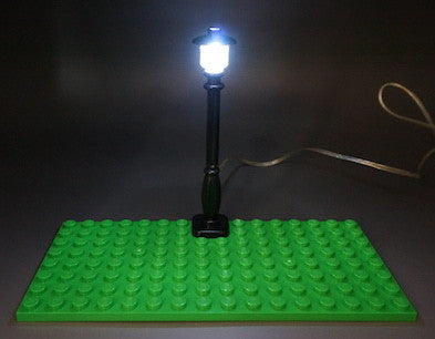 Brick Loot LED Lighting for LEGO Cities - Black Street Lamp / Lamp Post Light, powered through USB. The light in this photo is on.  Green base plate (pictured) not included.