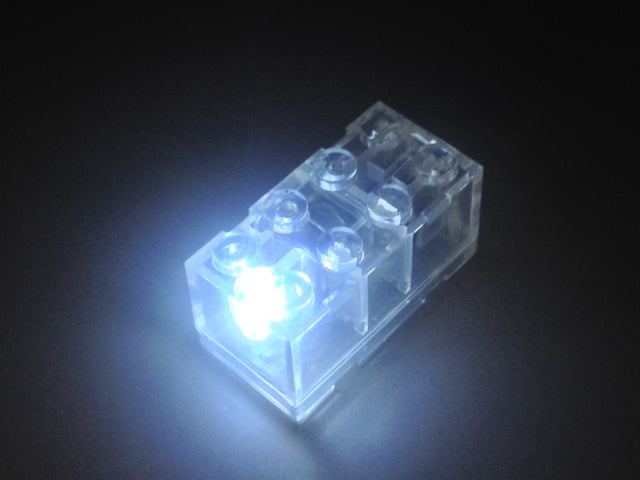 Brick Loot Light Up Clear 2x4 Brick - with RGB LED. This brick flashes Red, Green, Blue, White (white is pictured, here).  2 AG3 batteries are included in the brick.