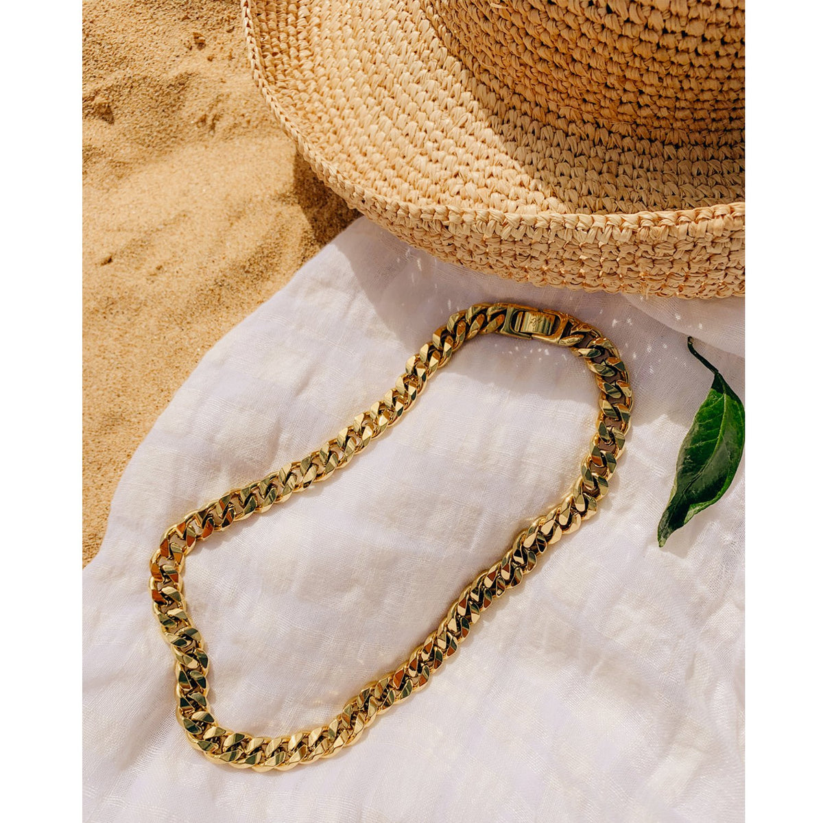 A flatlay of a chunky curb chain necklace laying on a blanket in the sand