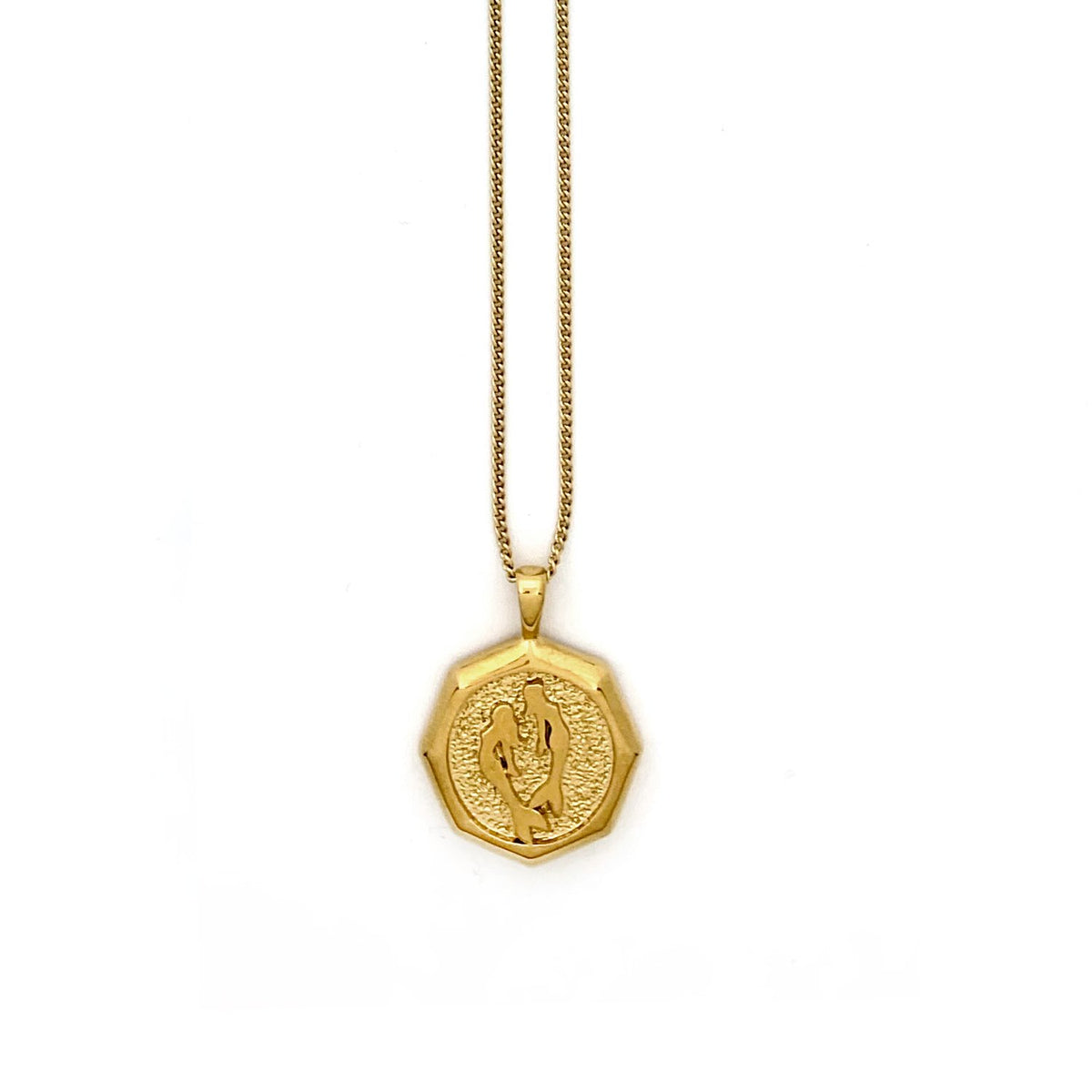 A close-up of a gold pendant necklace in an octagon shape with two mermaids