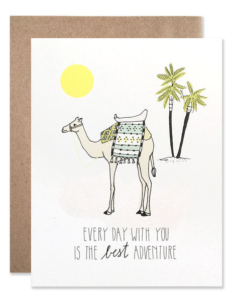 camel with saddle and blanket standing in the desert with palm trees and sun written underneath is Every Day With You is The Best Adventure. Illustrated by Hartland Brooklyn.