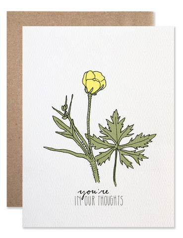 Single yellow buttercup bud with 'you're in our thoughts' written below. Illustration by Hartland Brooklyn.