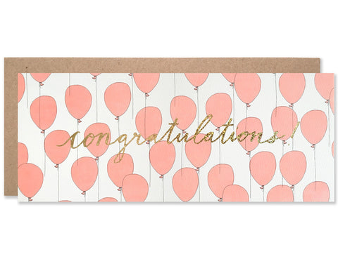 Congratulations script centered and written in gold glitter foil with a neon red balloon pattern behind it. Illustration and handwriting by Hartland Brooklyn.