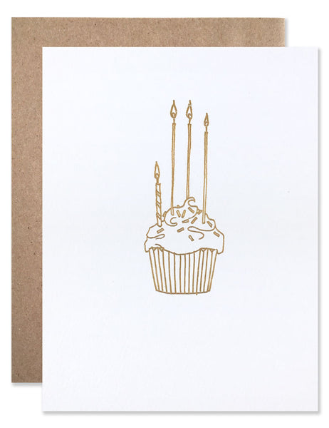 Gold foil cupcake with three tall candles and one short candle. Illustrated by Hartland Brooklyn.