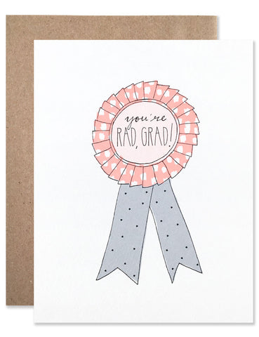 Pink and blue ribbon award with 'You're Rad Grad' in the center of the ribbon. Illustration by Hartland Brooklyn