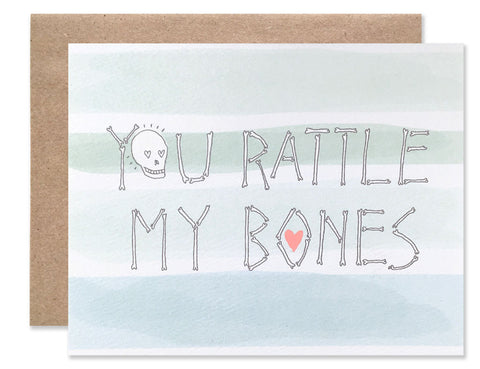 You rattle my bones written in hand illustrated bones with a background of waves of blue and green watercolor. Illustrated by Hartland Brooklyn