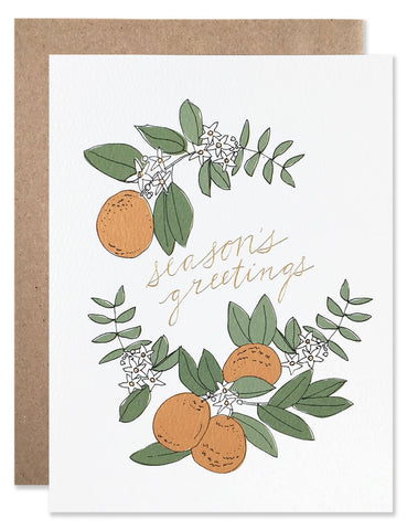 Season's greetings with oranges, green leaves and gold foil handwriting. Illustrated by Hartland Brooklyn.
