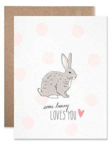 Illustration of a grey bunny with a background of pink polka dots with 'Some Bunny Loves You'. Illustrated by Hartland Brooklyn