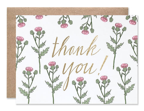 Gold foil stamped cursive 'thank you!' on a background of pink thistles. Illustrated by Hartland Brooklyn