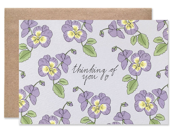 Purple violets on a purple background with Thinking of You written in the center. Illustration by Hartland Brooklyn